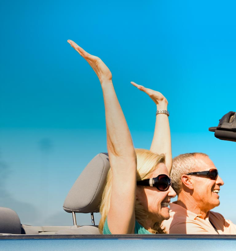 Happy older couple in convertible with hands raised.