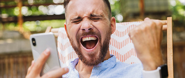 A man with happy expression holding a phone.