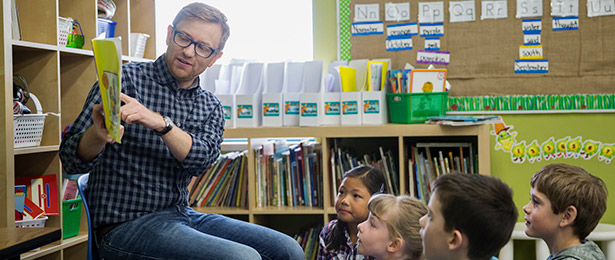 A teacher reading to young students.