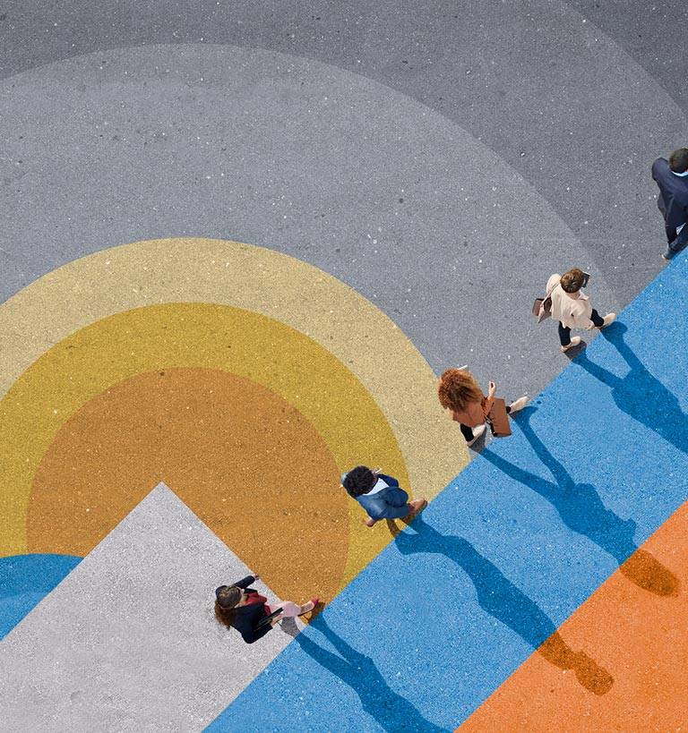 An overhead shot of 5 people walking in a line on a colorful background.