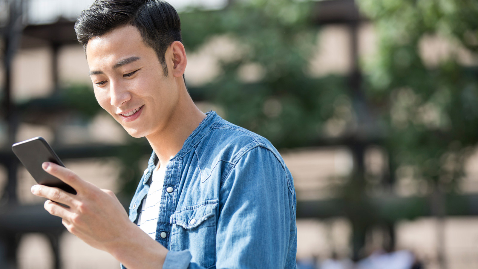 A young man looking at this cell phone.