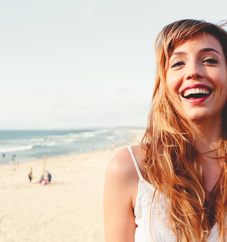 A smiling woman on the beach.