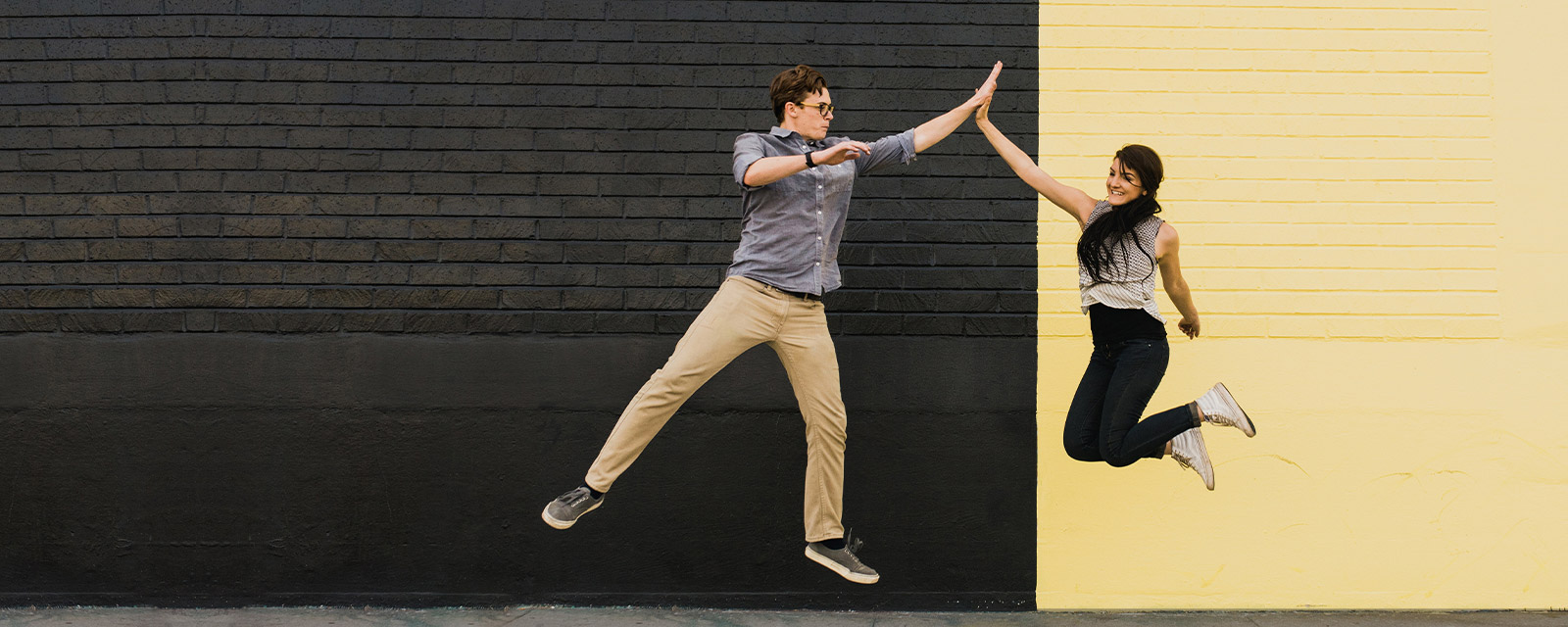 Two people jumping and high-fiving.