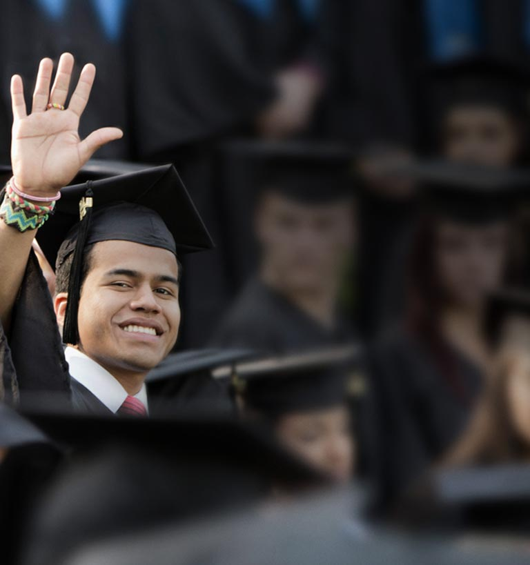A young man in graduation gown waving towards the camera.