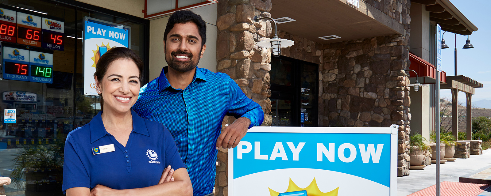 Two California Lottery retailers standing outside of a California Lottery retail store.